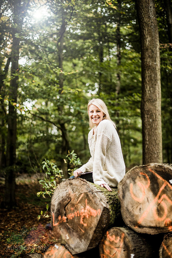 Portrait of happy woman sitting on stack of logs in the forest with tablet
