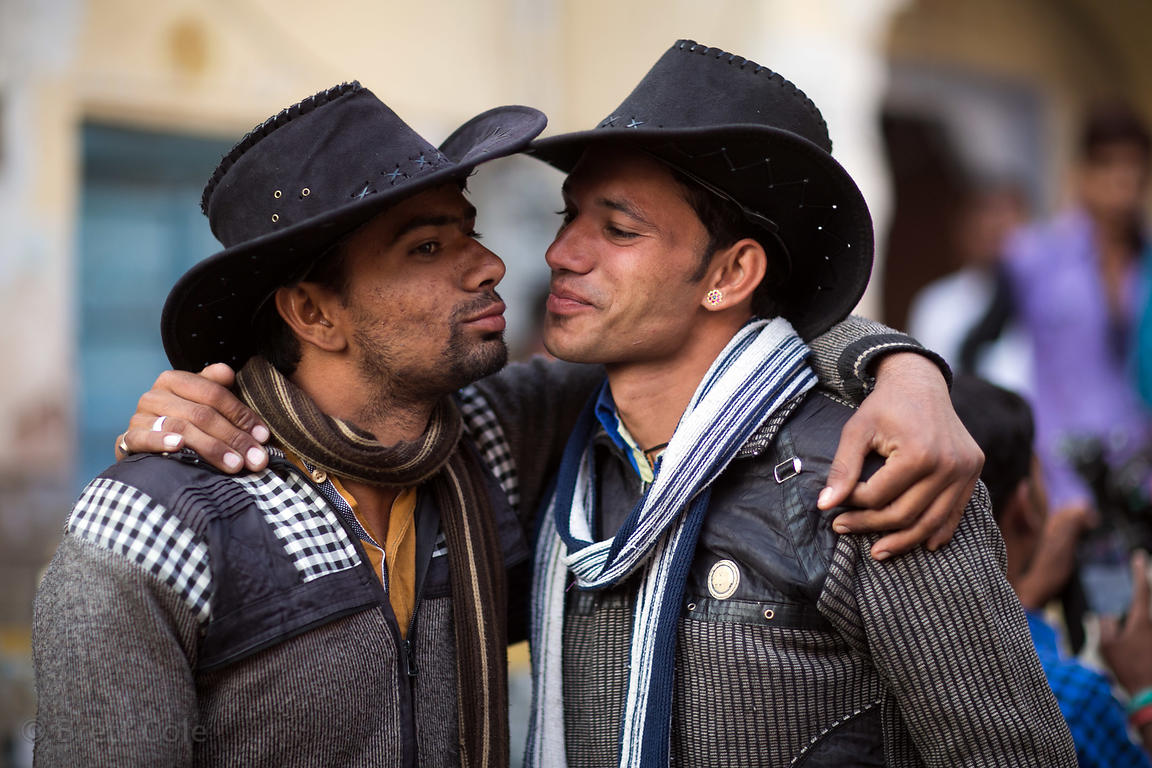 Two cowboys jokingly kiss in Pushkar, Rajasthan, India