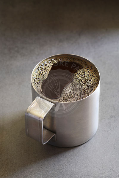 Fresh coffee in an aluminum mug on rustic background