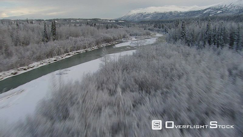 Flying above icy river's forested banks in Alaska