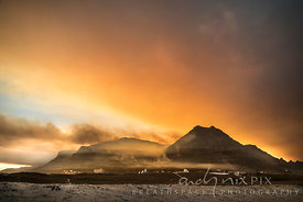 A ring of flames moves down the mountain slope above Muizenberg Village, a thick cloud of orange smoke in the sky