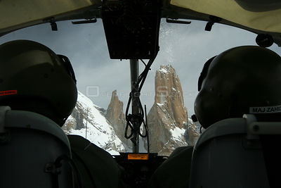 Rear view of pilots and Trango towers in the Karakoram Mountains, Himalayas, Pakistan, from Pakistani military helicopter, fo...