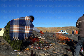 A woman puts coca leaves on burning offerings (called k'oas) to Pachamama, La Cumbre, Cordillera Real, Bolivia