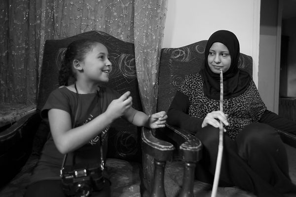 Rayan, 10 ans, discute avec sa mère pendant qu'elle fume la chicha, camp de Chatila, Liban / Rayan, 10, chats with her mother...