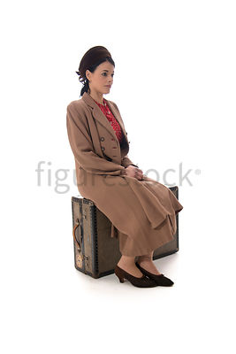 A 1940's woman in a hat and coat, sitting on a suitcase – shot from mid-level.