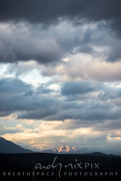 Sunlight on mountain in distance, cloudy sky at sunset