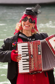 Accordian Player from the Trentina Museum in the Venice Carnival Water Parade  on the Rio di Cannaregio Canal