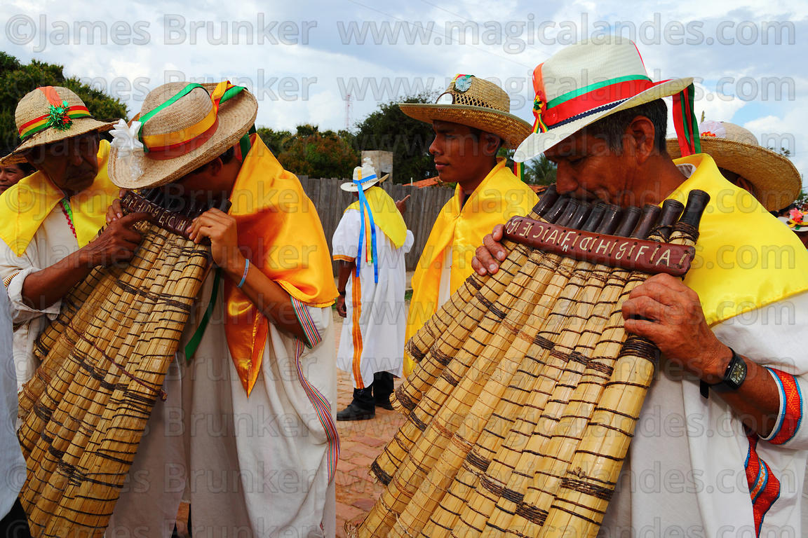 Young musician (L) being shown how to play the Bajon Grande during main procession, San Ignacio de Moxos, Bolivia