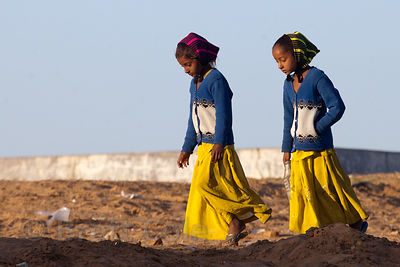 Two girls walk the mela ground in early morning, Pushkar, Rajasthan, India