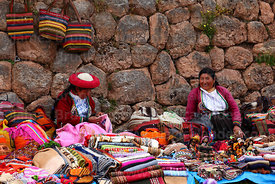 Quechua women wearing traditional dress selling handicrafts in front of Inca wall at Chinchero market, Sacred Valley, Cusco R...