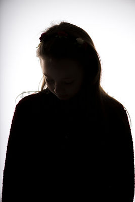 A Figurestock image of a girl in silhouette, standing, looking down – shot from eye level.