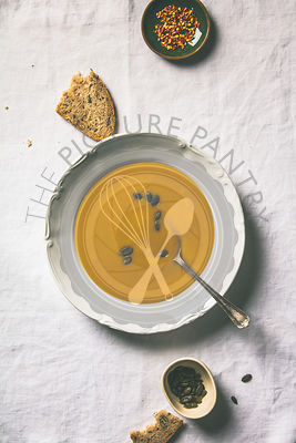 Autumn pumpkin cream soup on white tablecloth