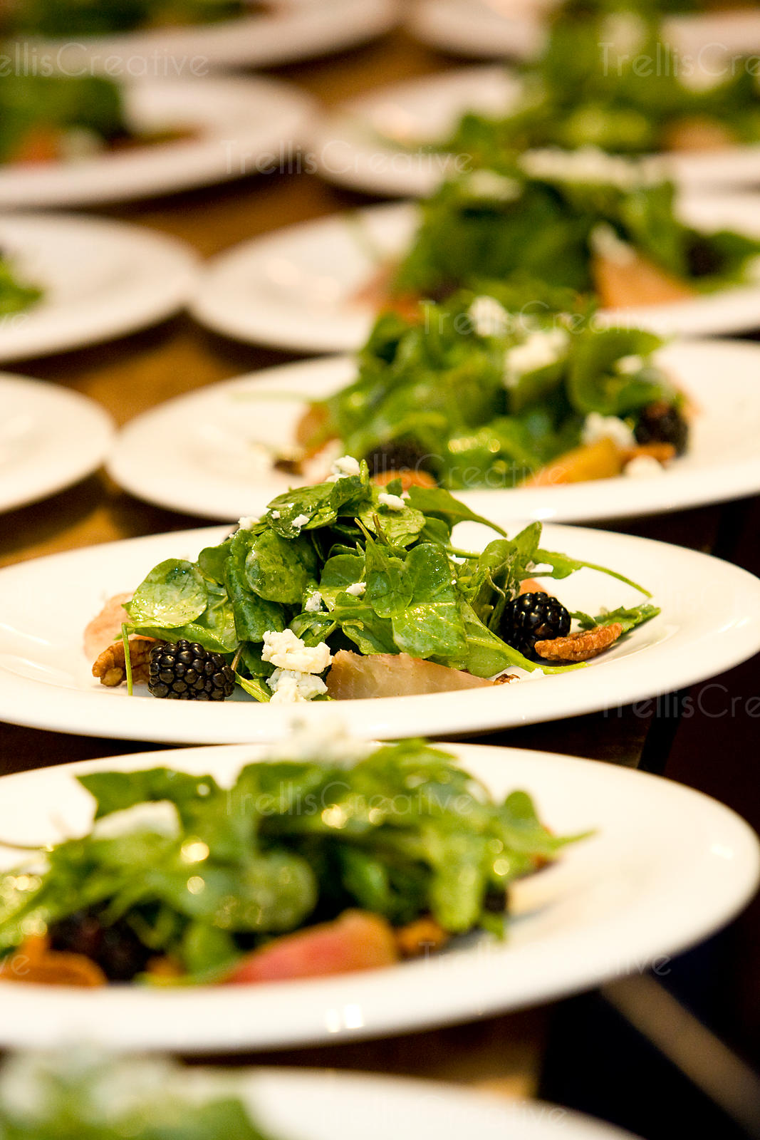 Many plates of spinach salad with goat cheese at a party