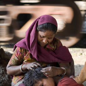 A mother picks fleas from her child's hair on a piece of waste ground next to the rail track where they live. New Delhi, India