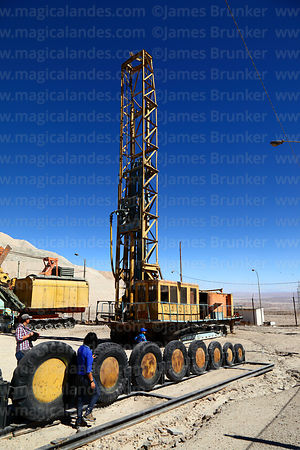 Disused blasthole drill and truck tyres on display near Chuquicamata mine, Region II, Chile