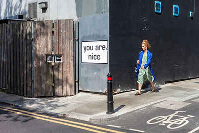 A Woman Walks Past A Humorous Slogan On A Street In Shoreditch,
