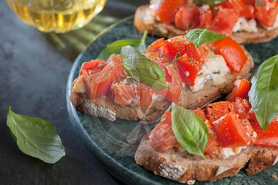 Italian tomato bruschetta with basil and olive oil on crusty slice of bread