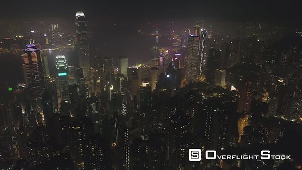 Illuminated Hong Kong Skyline and Victoria Harbour at Night. Aerial View. Drone is Flying Forward, Camera is Tilting Up. Esta...