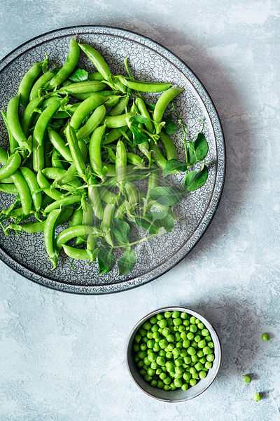 Green organic pea pods on a plate and shelled peas in a bowl.