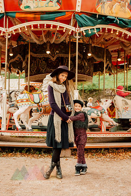 Happy young woman and little girl standing in front of children's carousel at fair