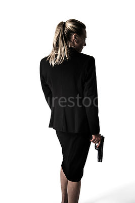 A silhouette of a blonde woman in a suit, holding a gun – shot from eye level.