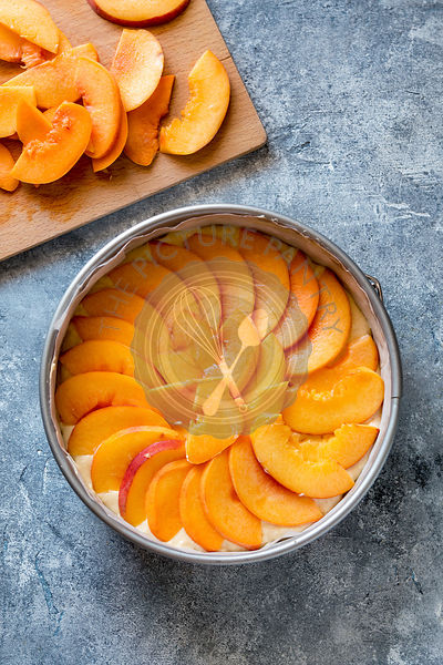 Fresh peach cake in the pan,ready to bake.Top view