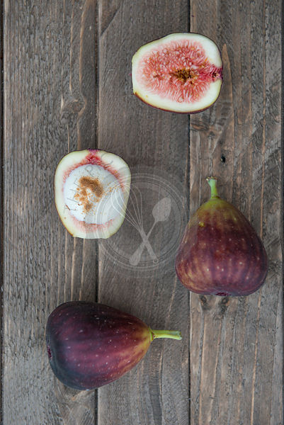 Halved figs on a wooden board, with natural yoghurt and cinnamon.