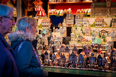 Senior Couple looking at Christmas Market Stall of Model Houses