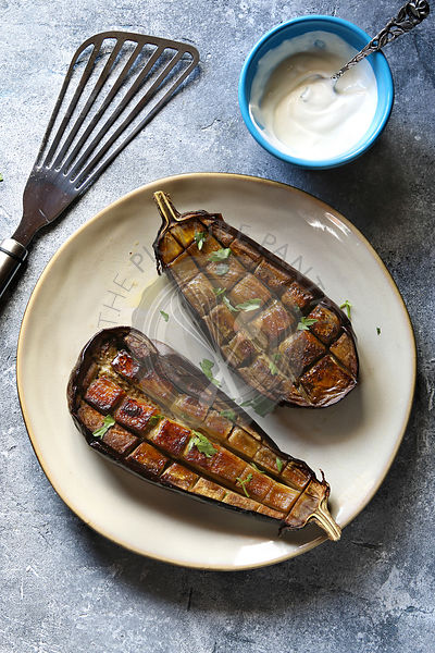 Roasted eggplant on a plate with garlic yogurt sauce .Top view