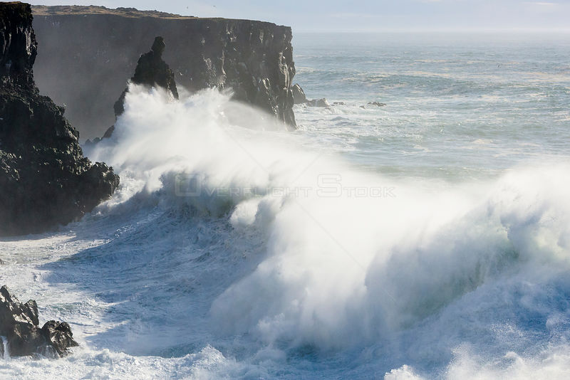 Storm waves breaking against cliffs at Svortuloft, Iceland.
