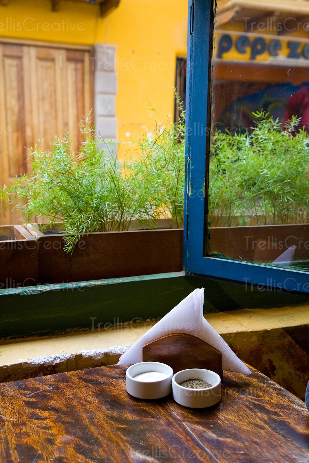 Napkin holder, salt and pepper sit on wooden table in front of open window of cafe