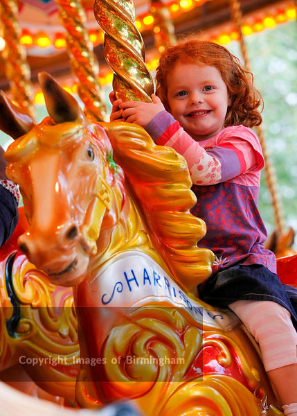 Three year old girl with red hair on a fairground carousel horse.