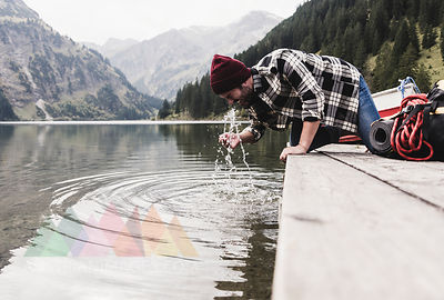 Austria, Tyrol, Alps, man kneeling on jetty refreshing at mountain lake