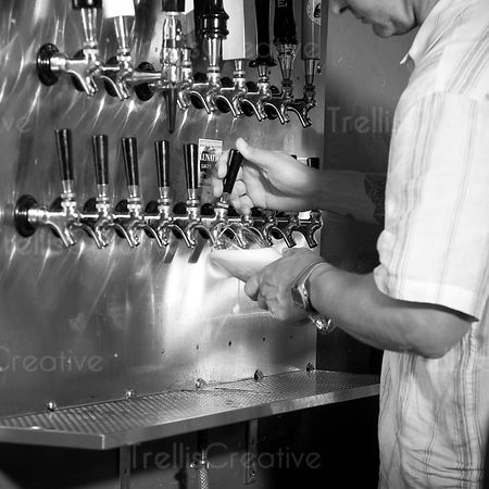 Close-up of bartender pouring beer from tap handles