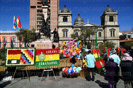 Stall selling inflatable toys for children and floral tributes for 16th July uprising anniversary celebrations at base of the Murillo Monument, Plaza Murillo, La Paz, Bolivia
