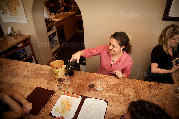 A smiling young woman pours a glass of red wine at a winery tasting room for tourists