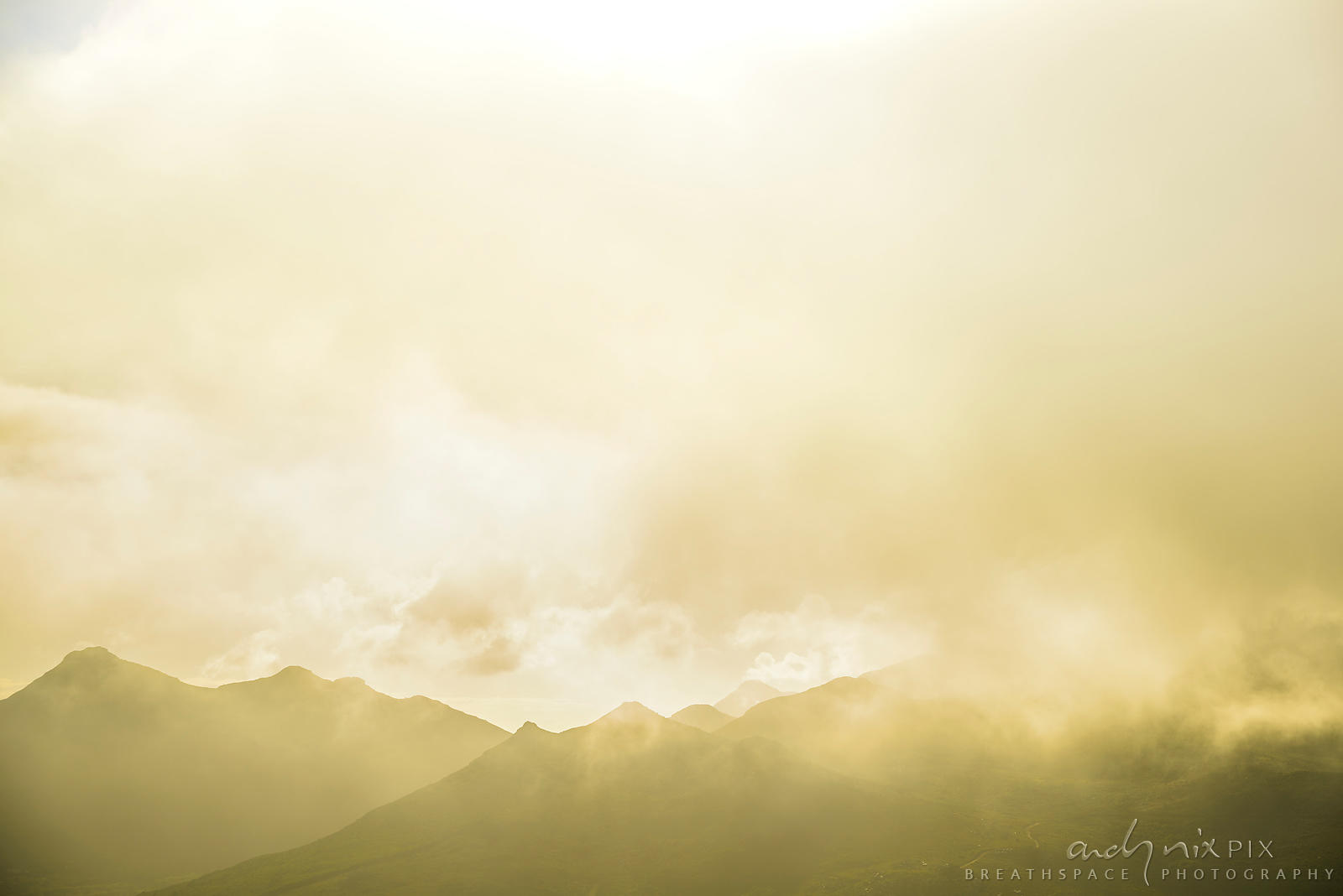 Soft sun light shining through blue tinged mist clouds rising above a silhouetted mountain range.