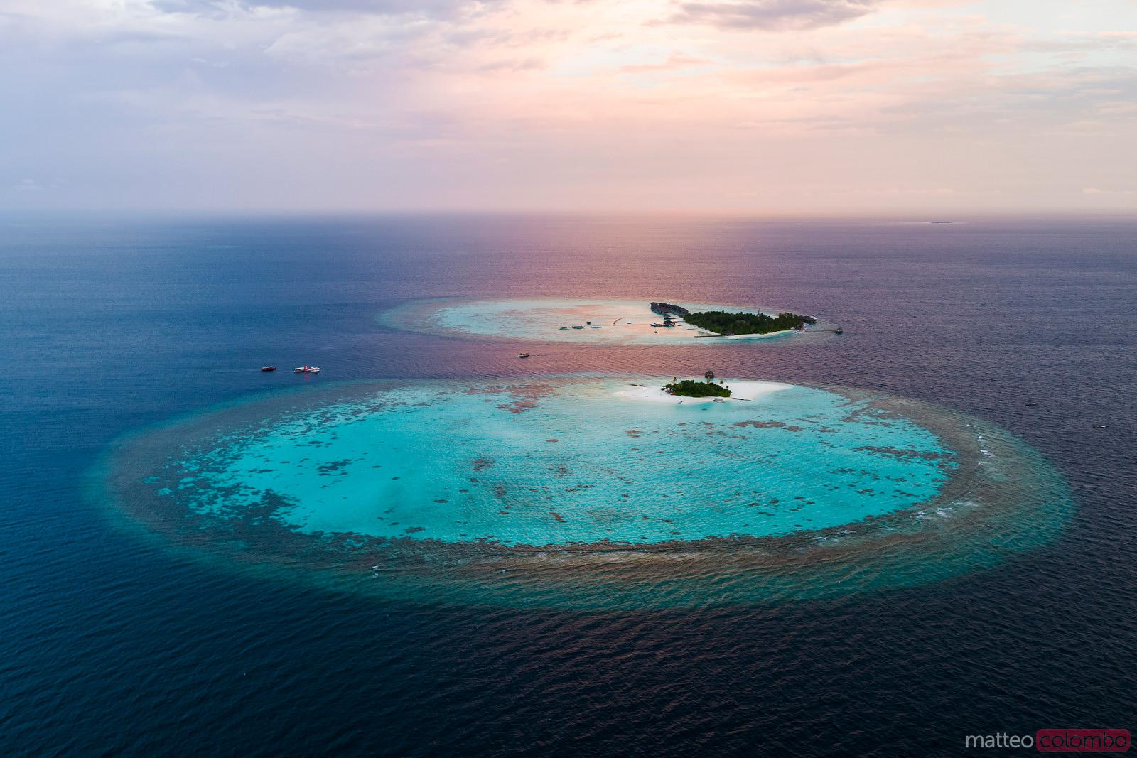 Aerial view of two islands in the Maldives at sunset