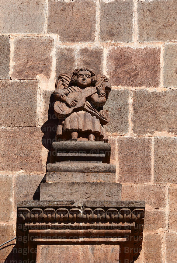 Detail of angel figure playing a charango or guitar on main facade of cathedral, Puno, Peru