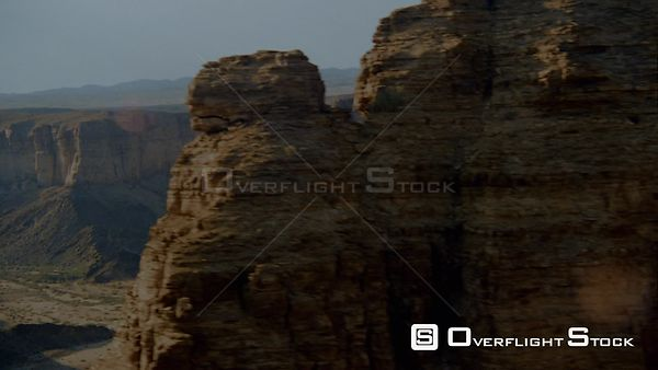 Aerial side of rocky outcrop and single weathered pillar of rock, wide long shot dry riverbed in desert terrain and mountain ...