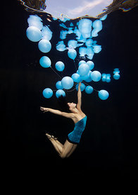 BodyArt dancer Michelle Jongeel underwater withan array of blue balloons against a black backdrop