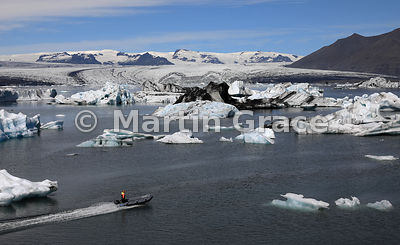 Person in inflatable dinghy with icebergs in Jokulsarlon glacier lagoon, Austurland (Eastern Region, East Iceland), Iceland
