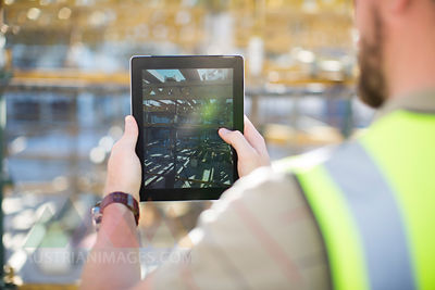 Construction worker using digital tablet on construction site