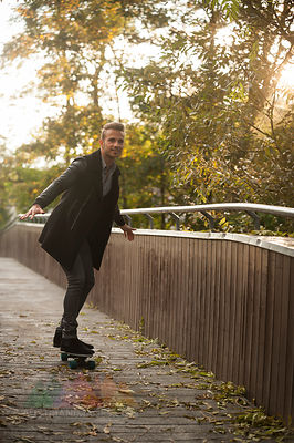 Smiling young man skateboarding on a footbridge in autumn