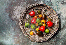 Ripe fresh colorful tomatoes on wicker tray on metal background