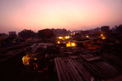 India - New Delhi - A moon and a pink sky over the shacks of Shadipur