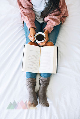 Woman with cup of coffee and book relaxing on bed, partial view