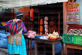 Aymara woman shopping at butchers shop in street market, Coroico, North Yungas province, Bolivia