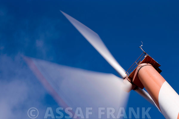 Rotating Wind Turbile Blades in Slow shutter speed on a background of blue skies.