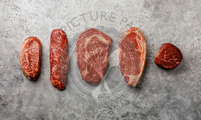 Variety of Raw Black Angus Prime meat steaks Top Blade, Denver, Rib Eye, Striploin, Tenderloin fillet Mignon on gray background